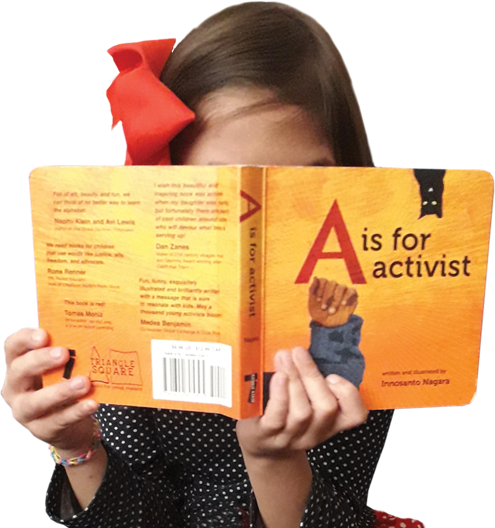 Young girl reading a book titled A is for Activist